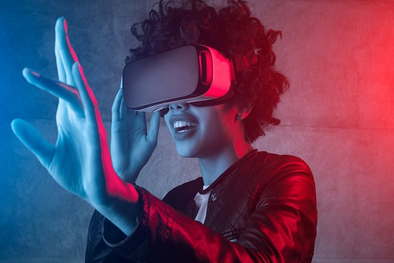 Curly woman in leather jacket using VR glasses while touching air in colorful neon lights